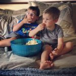 dzieci ogldające telewizję i jedzące popkorn